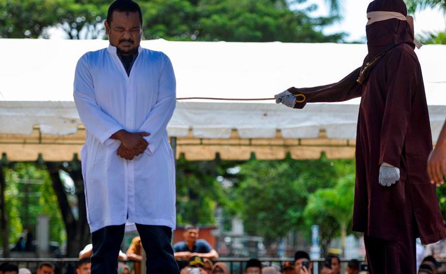 Um indonésio apanha em público após ser flagrado em andando em extreita proximidade com a namorada em Banda Aceh.
