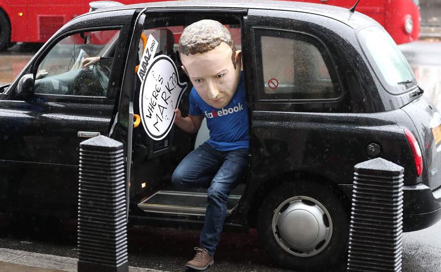 Manifestante usando uma máscara do CEO do facebook, Mark Zuckerberg, questiona a recusa de recusa de Zuckerberg de fornecer provas para a investigação levada a cabo pelo Parlamento inglês sobre desinformação e 'falsas notícias'.