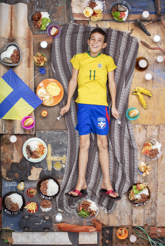 """Davi, Brasília, 2018: """"Davi com a comida que comeu em uma semana e sua pipa. O conjunto é feito a partir de materiais coletados da favela Chácara Santa Luzia, em Brasília, onde moram Davi e sua família, uma comunidade de mais de 12 mil pessoas"""""""