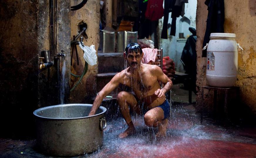 Homem se banha em casa em Nova Déli.