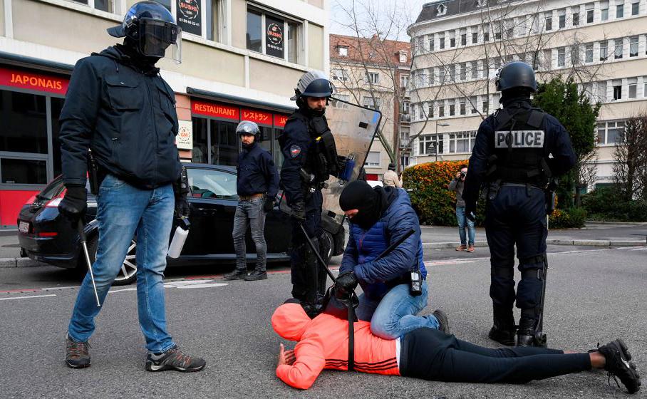 Agentes da polícia francesas detem um homem em uma rua de Mulhouse durante uma manifestação de estudantes secundaristas que protestam contra as reformas de educação.