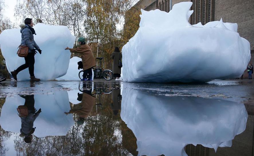 Visitantes interagem com blocos de gelo em derretimento numa instalação intitulada 'Ice Watch' criada pelo artista dinamarquês-Islandês Olafur Eliasson e o geólogo Groenlandês Minik Rosing em frente ao Museu Tate Modern em Londres.