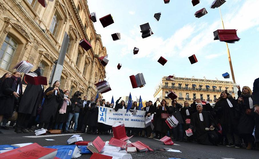 Advogados jogam livros de direito para cima durante manifestação contra o último plano de reforma da justiça, em Marselha, sul da França