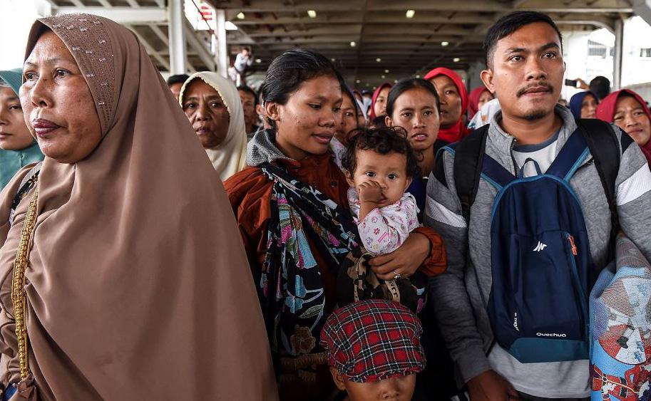 """Moradores desembarcam de um ferry após serem evacuados da ilha de Sebesi, em Bakauheni na província de Lampung após o tsunami de 22 de dezembro, causado pela atividade do vulcão conhecido como o """"filho"""" do Krakatoa."""
