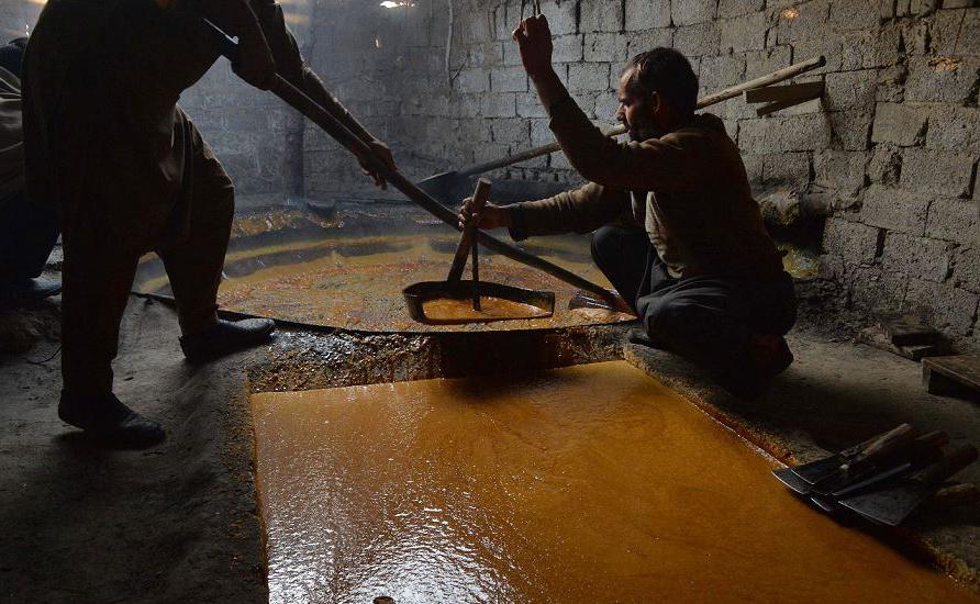 Trabalhadores afegãos preparam açúcar mascavo em uma tradicional fábrica na província de Kama, distrito de Nangarhar, a leste de Jalalabad.