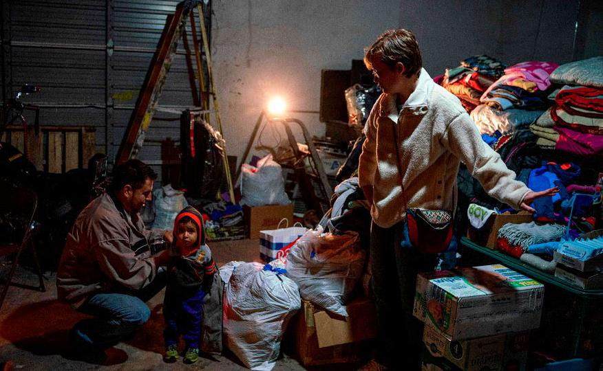 Augusto Mendoza da Guatemala e seu filho de um e um meio ano de idade, Dillon recebem  roupas e a comida de voluntários no Rock House café no centro de El Paso, depois de passar cinco dias na detenção de migração no Novo México.
