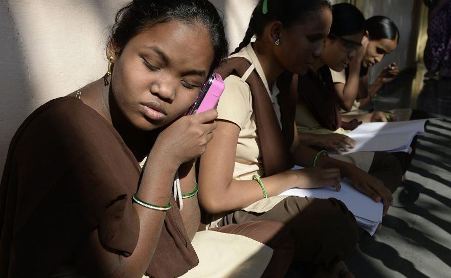 Estudantes indianas com deficiência visual ouvem um áudio libvro recontado pelos que o  leram em Braille no Santos Junior College para cegos em Hyderabad.