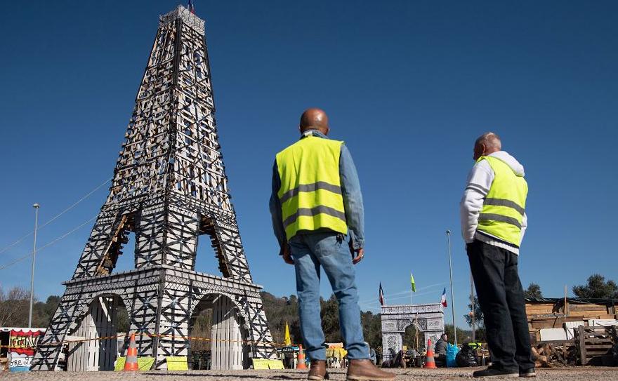 """Integrante do movimento """"Colete amarelo"""" se organizam ao lado de uma réplica da Torre Eiffel feita com 135 paletes de madeira, depois de 15 semanas consecutiva de protestos em todo o país contra as políticas do Presidente francês."""