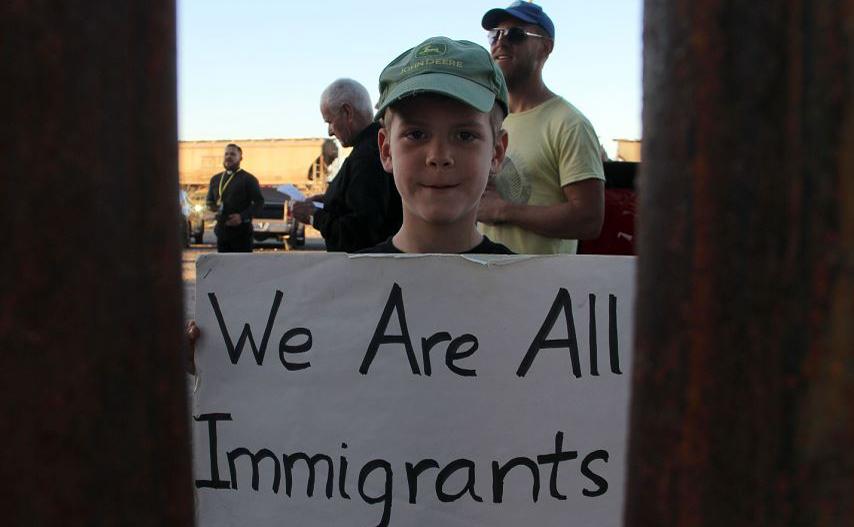 Um garoto americano junta-se a moradores de Anapra, um bairro na periferia de Ciudad Juarez, no México, durante uma cerimônia religiosa no muro da fronteira entre México-EUA.