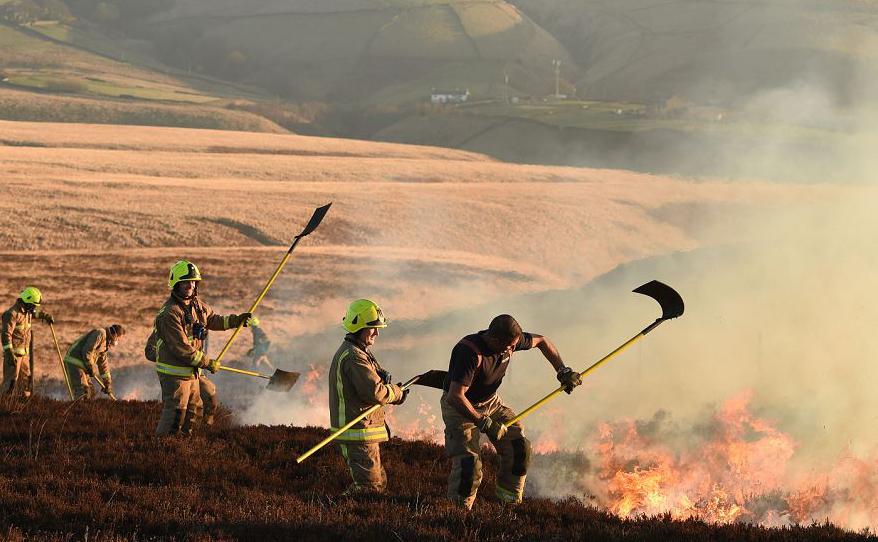 Bombeiros combatem um incêndio em Marsden, noroeste da Inglaterra.