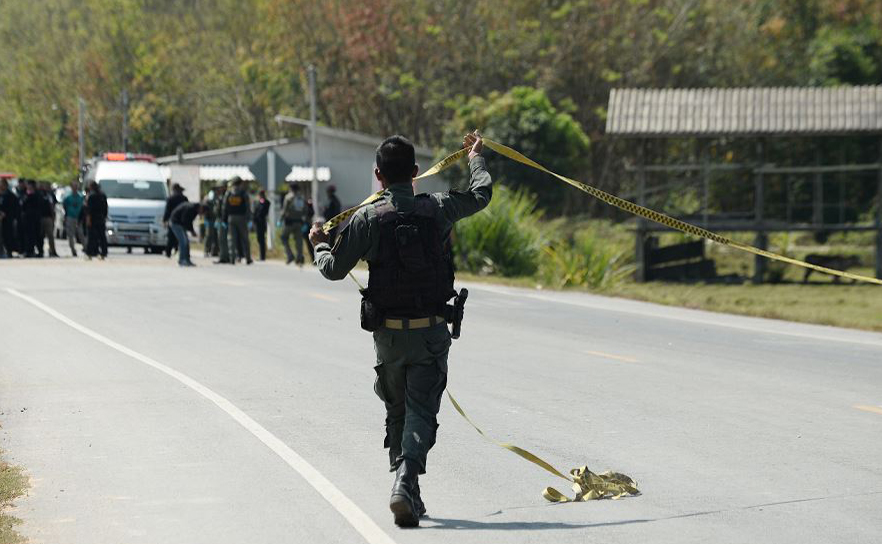Polícia tailandesa e investigadores militares inspecionam a área onde houve a explosão de uma bomba na província de Narathiwat na Tailândia.