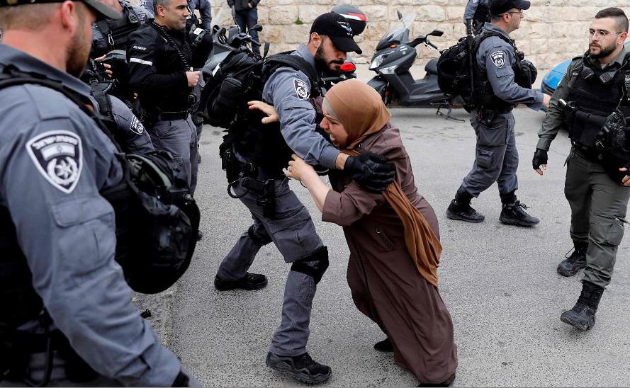 Um policial israelita empurra uma mulher Palestina após terem fechado o acesso à Mesquita de al-Aqsa, na cidade velha de Jerusalém.