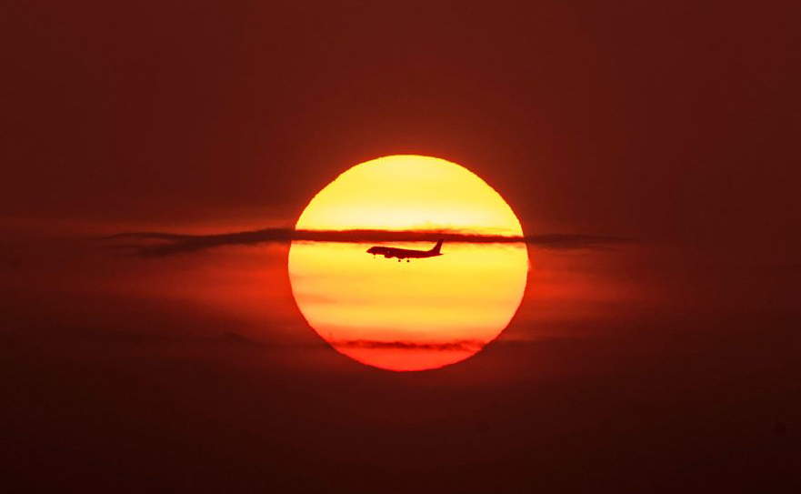 Avião voa sobre a Baía do Panamá, na cidade do Panamá durante o nascer do sol.