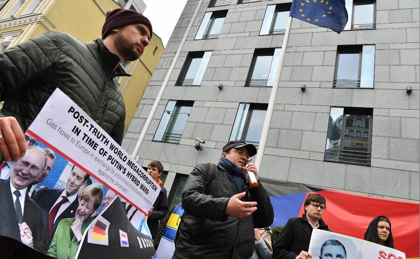 Manifestantes protestam contra o fim das sanções da Alemanha contra a Rússia e pedem que se aumente a pressão para libertar os presos ucranianos. São 97 presos políticos ucranianos, bem como mais de 120 prisioneiros de guerra e reféns civis no Donb