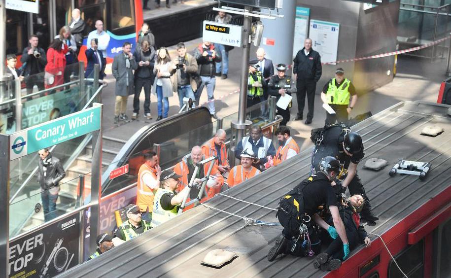 Manifestante ambientalista é retirada  pela polícia após se auto-colar num vagão de trem na  estação de Canary wharf, no terceiro dia de protestos em Londres.