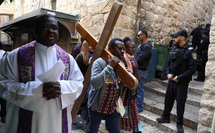 Peregrino carrega uma cruz de madeira ao longo da Via Dolorosa (caminho de sofrimento) na cidade velha de Jerusalém durante a procissão de sexta-feira.