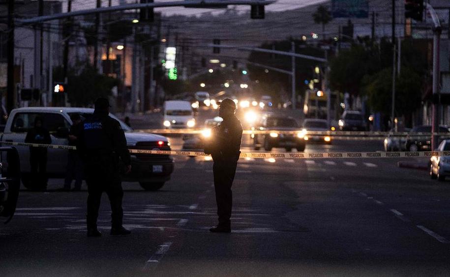 Policiais isolam a cena do crime, onde um homem foi morto a tiros no centro da cidade de Tijuana, estado da Baixa Califórnia, México.
