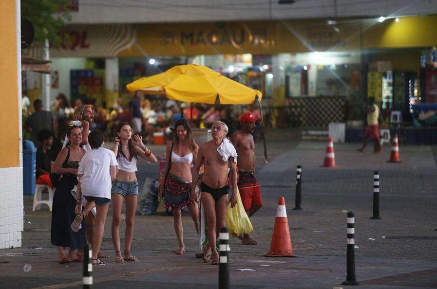 Artista e amigos deixam a praia pouco antes do pôr do sol