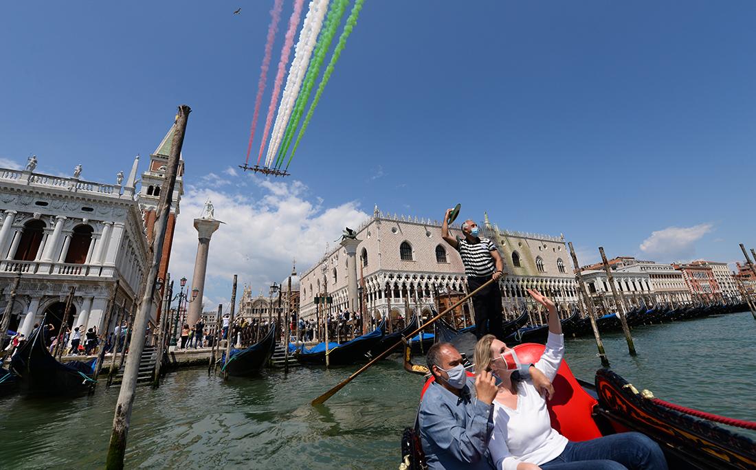 Em Veneza, na Itália, pessoas passeiam de gôndola e registram as acrobacias aéreas.