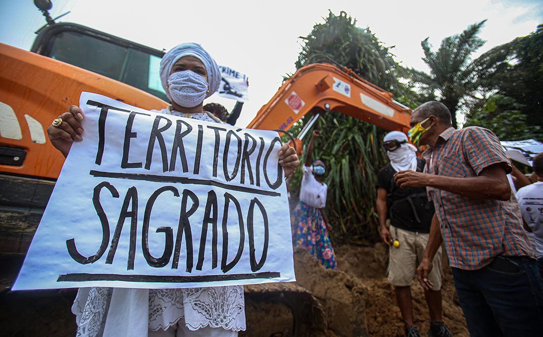 Manifestantes cercaram a retroescavadeira que trabalhava no local com cartazes pedindo a paralisação das obras, respeito à cultura local e ao povo de matriz africana, que tem a lagoa como local sagrado.